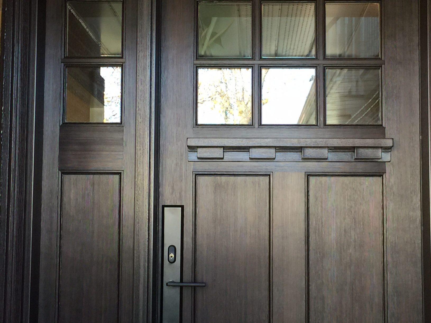 Dark wood front door with small windows
