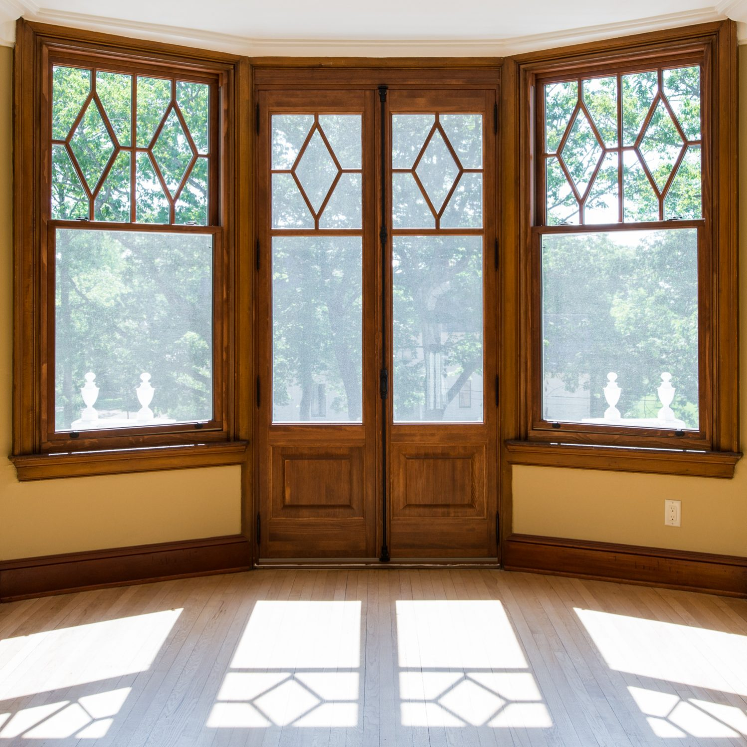 Two windows and door with sunlight pouring in