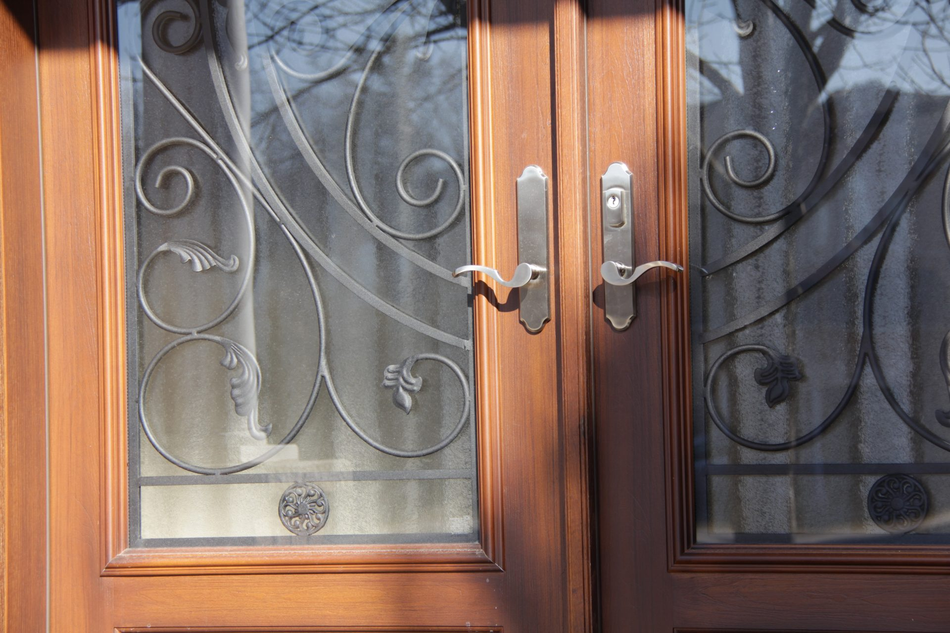 Front door with window panes and iron fixtures