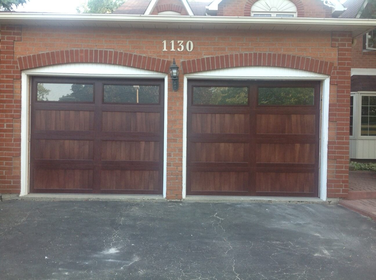 Faux wood grain steel garage doors in mahogany oakville for Wood grain garage doors